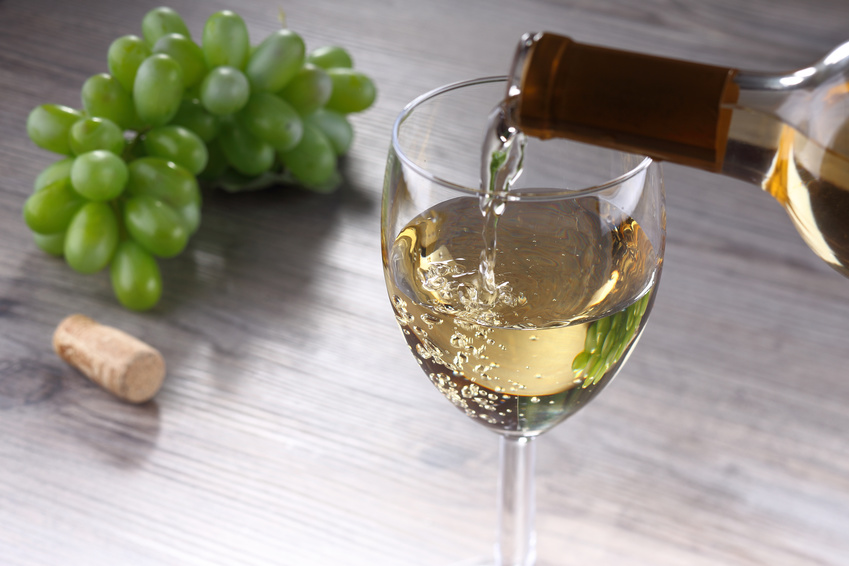 Pouring white wine into glass, tilt shift